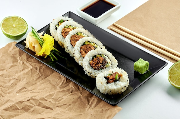 Classic japanese sushi rolls with filling. uramaki with cucumber, onion and baked salmon, served in a black plate