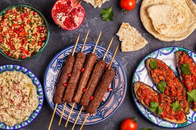 Классические шашлыки, салат табуле, баба гануш и запеченные баклажаны с соусом. традиционное ближневосточное или арабское блюдо. вид сверху.