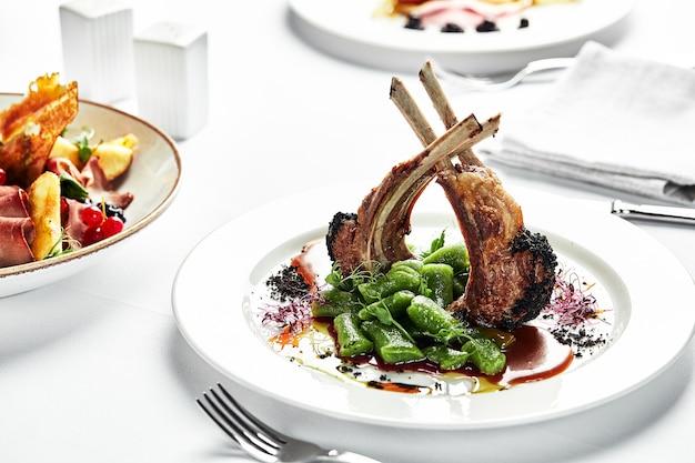 고전적인 양고기 요리는 프랑스 스타일로 제공되며, 스튜 콩 꼬투리가 있는 하얀 접시에 구운 양고기 랙. 요리사의 양고기 랙을 제공하는 레스토랑.
