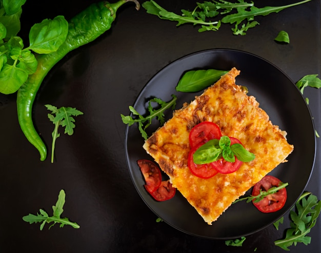 Classic lasagna with bolognese sauce on dark surface