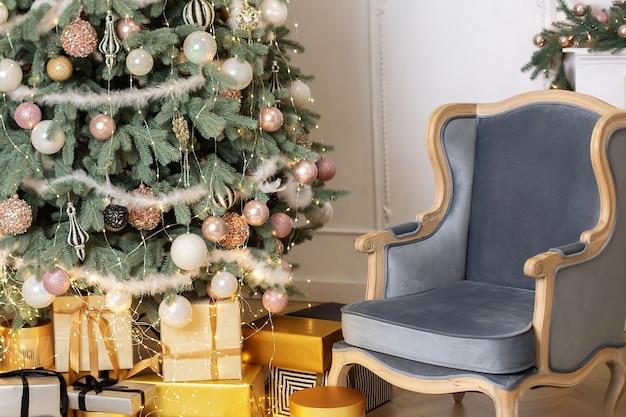 青いアームチェアと装飾されたシックなクリスマスツリーギフトを備えたクラシックなリビングルームのインテリア