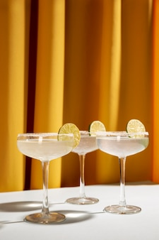 Classic margarita cocktails with salty rim on table with lemon