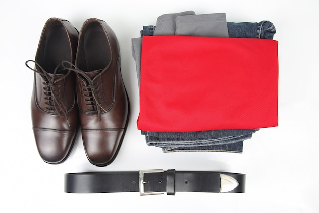 Classic men's brown shoes, belt and clothes on white