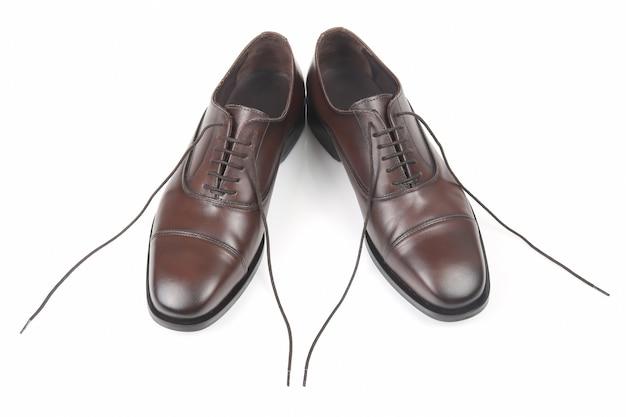 白いテーブルの上の古典的な男性の茶色の靴
