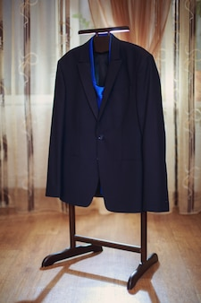 Classic men's jacket with blue tie on the wooden hanger in hotel room . designer men's jacket with close up indoor. showcase for men's store. men's clothing store. male morning close up