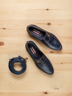 Classic men's shoes and a trouser belt made of dark blue leather on a background of light boards, top view. vertical arrangement