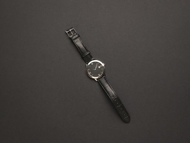 Классические мужские часы с кожаным ремешком на черном фоне. модный и стильный мужской аксессуар.