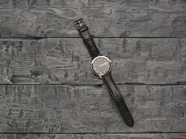 木製の背景に手でクラシックなメンズウォッチ。
