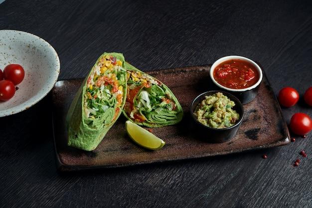 Классическая мексиканская кухня - буррито с запеченным сладким перцем, рисом, бобами в красной лепешке на белой тарелке. вкусно закрыть. выборочный фокус. быстрое питание. вегетарианская шаурма