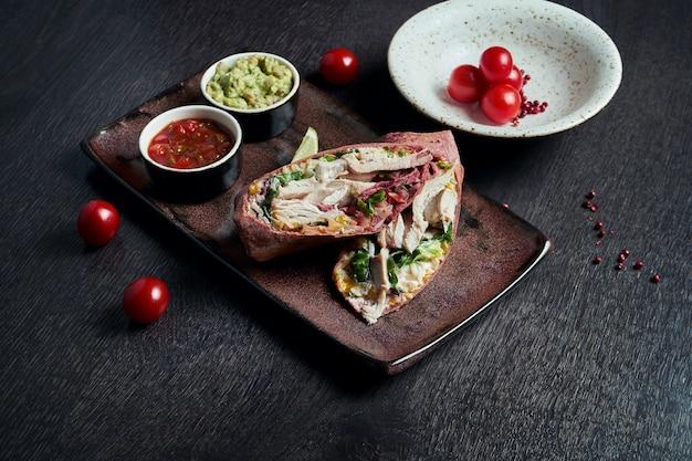 Классическая мексиканская кухня - буррито с курицей, рисом, фасолью в красной лепешке на белой тарелке. вкусно закрыть. выборочный фокус. быстрое питание. шаурмой