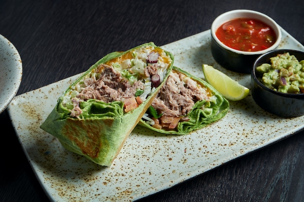 古典的なメキシコ料理-スモークポーク、ライス、白い皿に赤いトルティーヤの豆のブリトー。おいしいクローズアップ。セレクティブフォーカス。ファストフード。シャワルマ