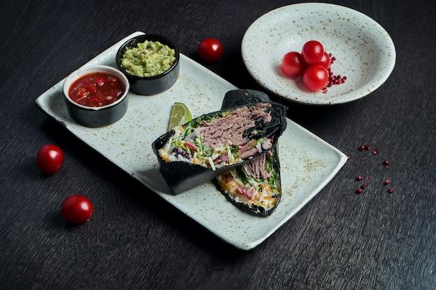 古典的なメキシコ料理-白いプレートに黒のトルティーヤで煮込んだ牛肉、米、豆のブリトー。おいしいクローズアップ。セレクティブフォーカス。ファストフード。シャワルマ
