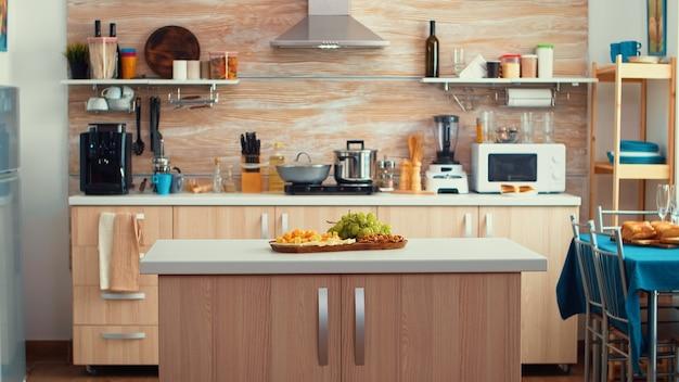 真ん中にテーブルがあり、素敵な木のディテールと寄木細工の床のあるクラシックでモダンなキッチン。ディナールーム、オープンスペース、中央にダイニングテーブルを備えたデザインの豪華な建築住宅装飾