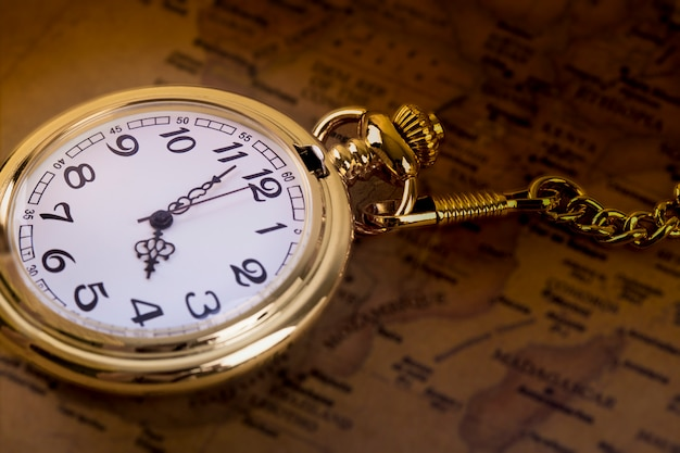 Classic necklace gold pocket watch on retro map