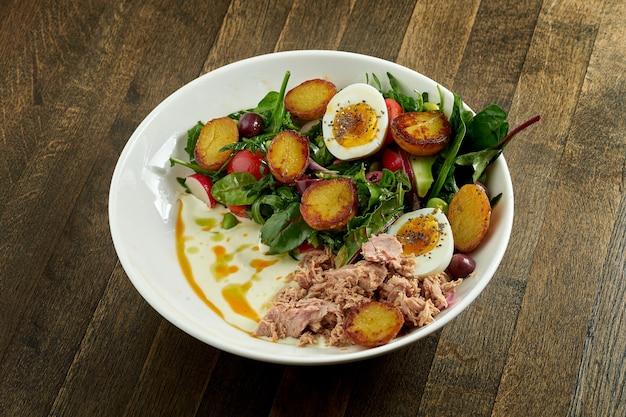 삶은 달걀, 감자, 참치, 올리브, 화이트 소스를 곁들인 클래식 니코 아즈 샐러드, 나무 접시에 흰 그릇에 담아 제공
