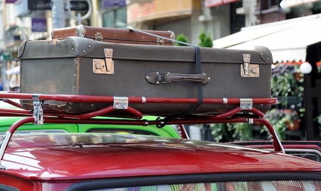 屋根にヴィンテージのスーツケースを着用したクラシックな古い車