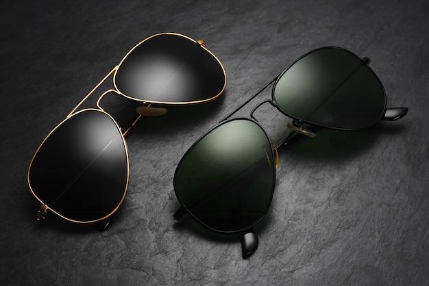 黒のスレートの背景にクラシックなオールドファッションアビエイターサングラス。上面図