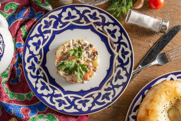 나무 테이블에 전통적인 우즈베키스탄 장식품이있는 세라믹 접시에 파슬리로 장식 된 마요네즈, 야채, 소시지를 곁들인 클래식 올리비에 샐러드.