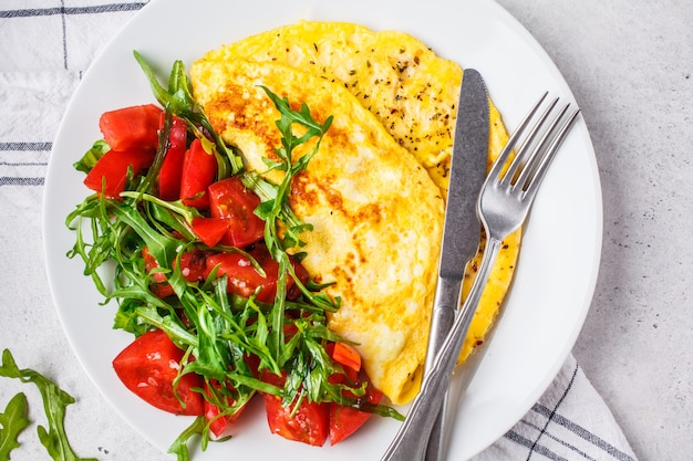 Classic omelet with cheese and tomatoes salad on white plate, top view.