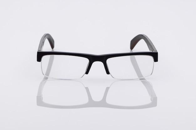 Классические оптические очки на светлой поверхности с отражением