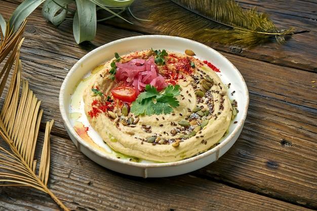古典的な東洋の前菜-木製のテーブルの白いプレートにひよこ豆のフムス。閉じる