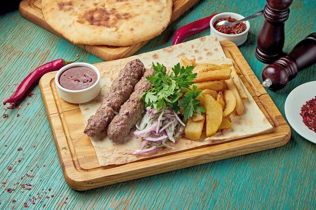 Классический восточный гриль на гриле люля кебаб с красным соусом и гарниром из печеного картофеля. восточная кухня