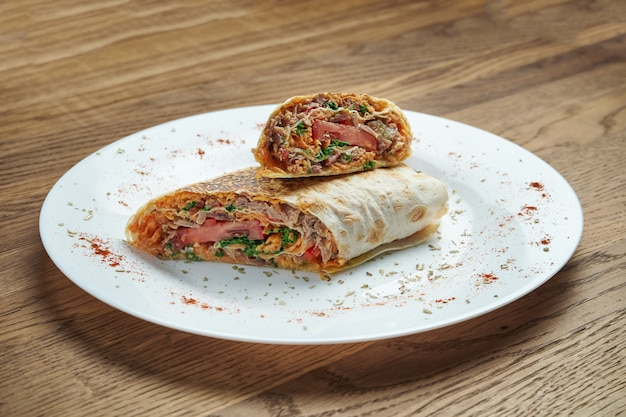 Classic oriental shawarma roll with minced meat. wooden background.