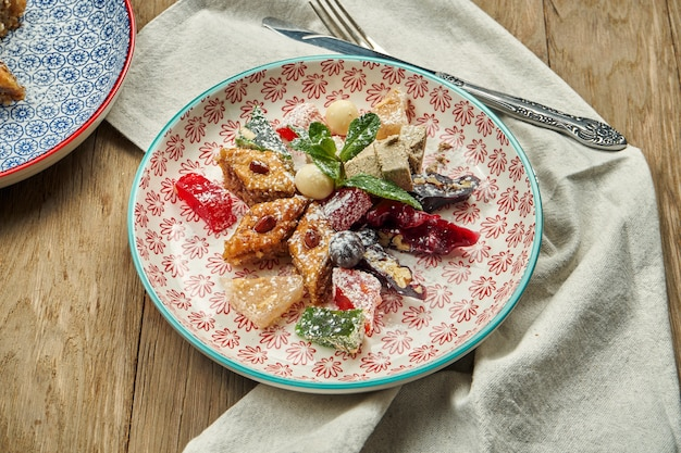 Classic oriental sweets - baklava with honey and nuts, turkish delight, churchkhela in a red ceramic plate on a wooden table