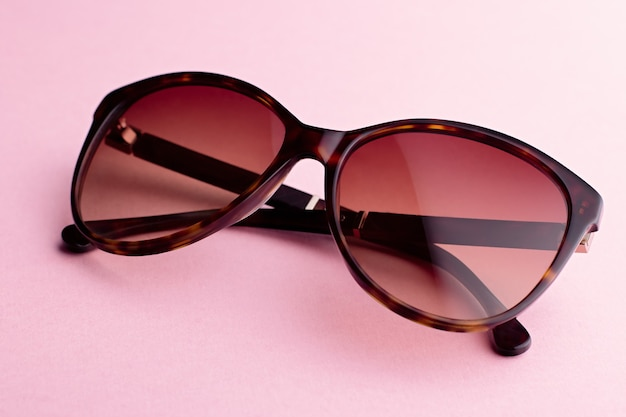 Classic oval oversized brown tortoise sunglasses closeup on pink background, top view. trendy retro shades