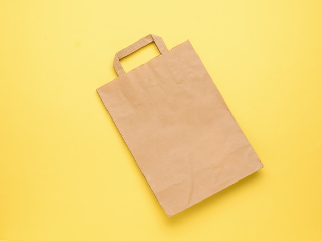 黄色の背景にハンドルが付いている古典的な紙袋。フラットレイ。