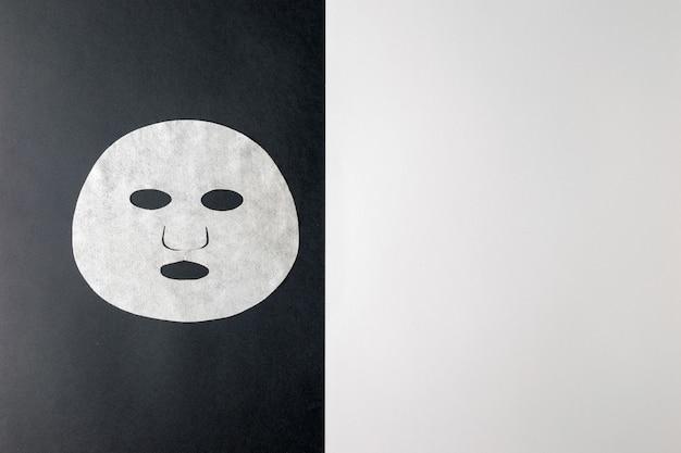 Классическая бумажная маска для лица на черно-белом фоне. маска для ухода за лицом и изменения внешности.