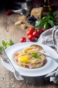 Классическая паста карбонара с желтком в тарелке на деревянном
