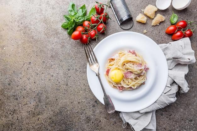 Классическая паста карбонара с желтком в тарелке