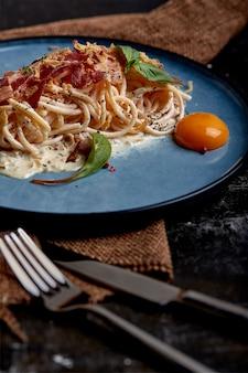 プレートに卵黄と古典的なパスタカルボナーラ。パスタは暗い表面の青い皿に並べた。イタリア料理のコンセプト、美しい料理、クローズアップ。