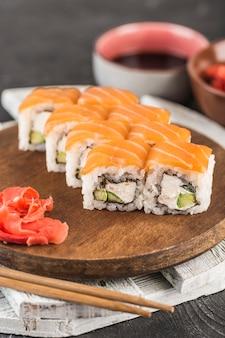 Классические суши-роллы филадельфия на деревянной доске с имбирем, соевым соусом и палочками для еды на темной поверхности