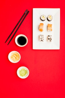 A classic philadelphia and sushi rolls with wasabi; ginger and soy sauce on white tray