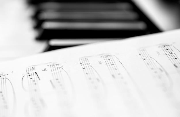 클래식 피아노와 악보. 흑백 사진, 음악적 배경