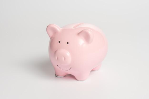 白い背景の上のお金のための古典的なピンクの貯金箱