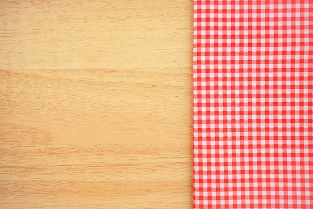 コピースペースのある木製の机の上の古典的なピンクの格子縞の生地またはテーブルクロス