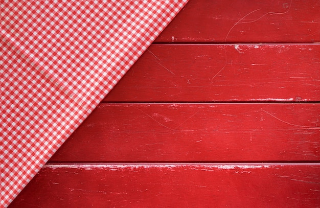 Classic pink plaid fabric or tablecloth on old red wood table with copy space