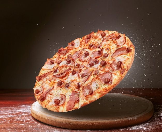 Classic pizza on a dark wooden table surface and a scattering of flour. pizza restaurant menu concept