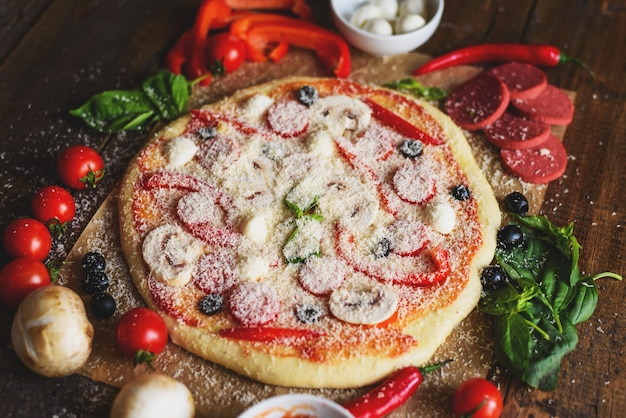 Classic pizza with vegetables and mushrooms with ingredients on wooden table