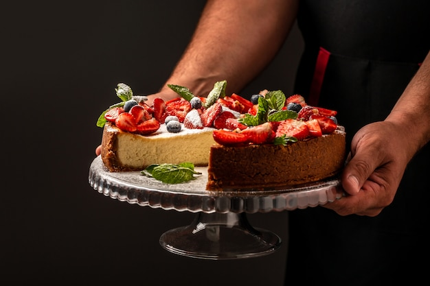 Classic plain new york cheesecake sliced in the hands of the chef closeup view, banner menu recipe place for text