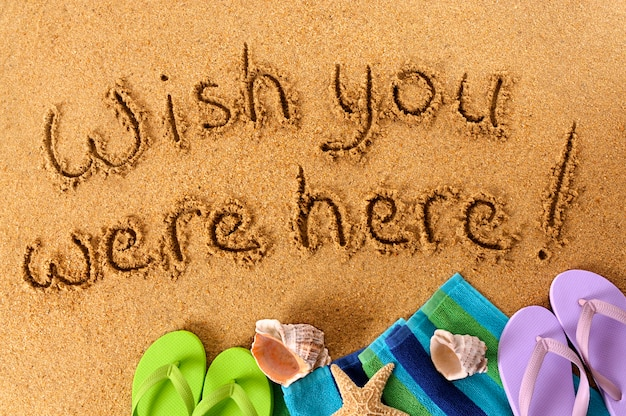 Classic postcard message written on a sandy beach, with beach towel, starfish and flip flops
