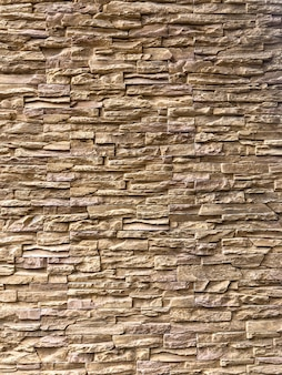 クラシックなランダムライトブラウンのレンガが壁に配置され、建物の外観を飾ります。