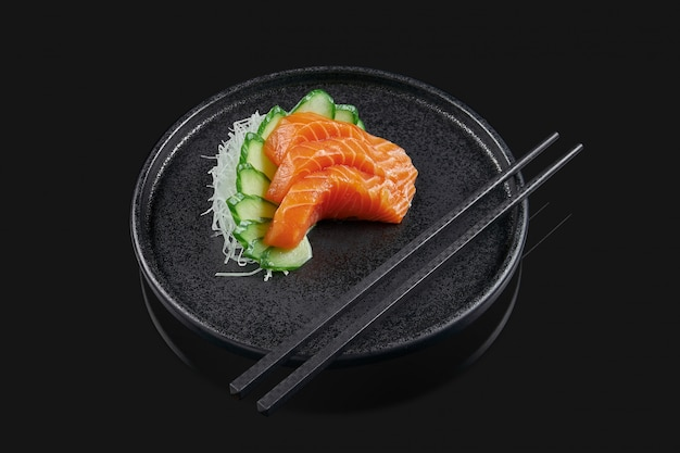 Classic raw salmon sashimi with cucumber on a stylish black ceramic plate on a black surface. japanese traditional food. photo for the menu