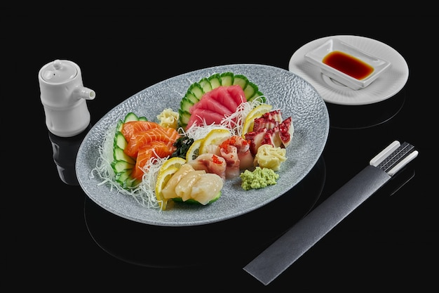 Classic raw set of sashimi octopus, salmon, sea bass, tuna, scallop with cucumber and daicon on grey ceramic plate on a black surface. japanese traditional food. photo for the menu