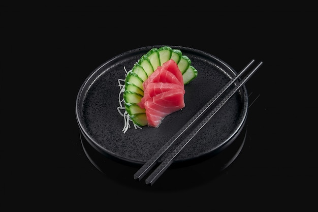 Classic raw tuna sashimi with daicon raddish on a stylish black ceramic plate on a black surface. japanese traditional food. photo for the menu