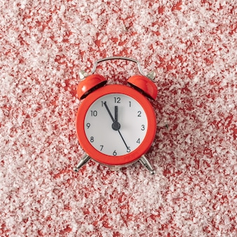 Classic retro alarm clock on a red background with white snow. minimal trend concept for christmas and new year.