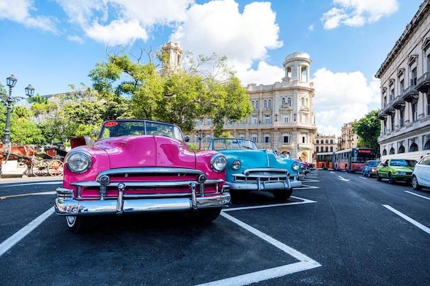 Классические ретро-автомобили chevrolet в разных ярких цветах припаркованы перед национальным музеем изящных искусств на площади, недалеко от памятника хосе марти.